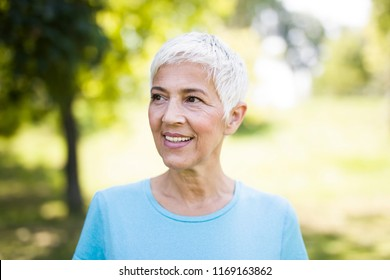 Portrait of a smiling sporty senior woman in a park at summer day