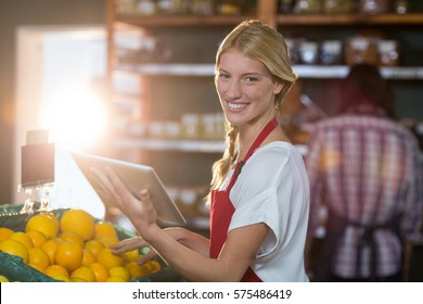 Portrait of smiling staff using digital tablet while checking fruits in organic section of supermarket
