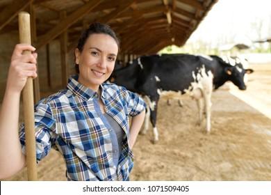 Portrait of smiling stock breeder standing in barn