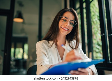 Portrait of a smiling student girl filling application form.