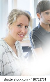 Portrait of smiling student girl working with classmate