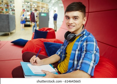 Portrait of smiling student resting on bean bag in creative workspace of modern college, studying and looking at camera, working with books