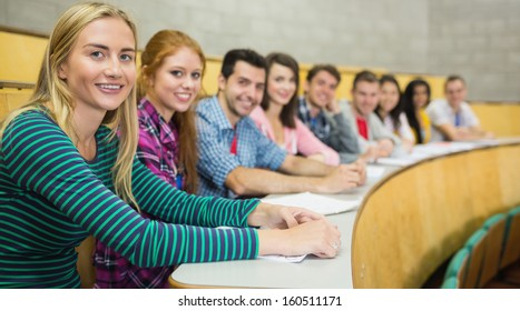 Portrait of smiling students sitting in a row at the college lecture hall
