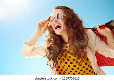 Portrait of smiling stylish woman in sunglasses and a light jacket looking into the distance with shopping bags against blue sky