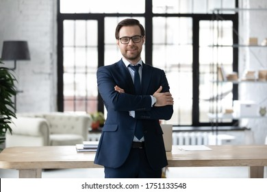 Portrait of smiling successful Caucasian businessman in formal suit glasses stand posing in modern office, happy young male boss or CEO look at camera, show confidence and power, leadership concept