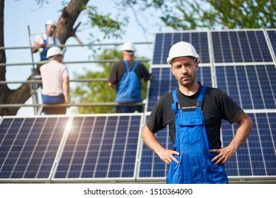 Portrait of smiling successful engineer technician standing in front of unfinished high exterior solar panel photo voltaic system blue shiny surface, with team of workers on high platform.