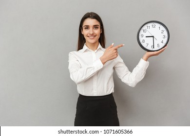Portrait of smiling successful woman in white shirt and black skirt pointing finger on round clock holding in hand isolated over gray background