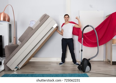 Portrait Of A Smiling Superhero Man Lifting The Couch With Woman