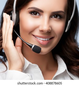 Portrait of smiling support female phone operator in headset, against grey background. Consulting and assistance service call center.