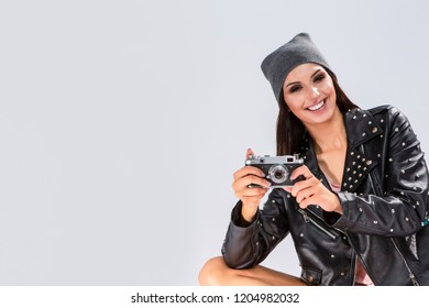 Portrait of Smiling Tanned Caucasian Brunette in Black Leather Jacket and Warm Hat Making Pictures With Old School Film Photocamera. Against White.Horizontal Image