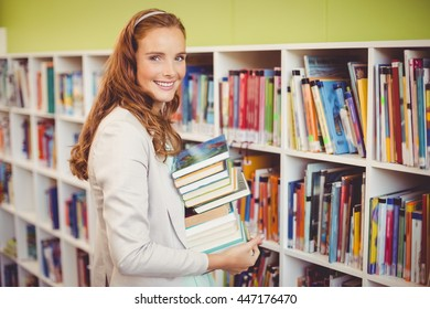 Portrait of smiling teacher holding a stack of books in library at school