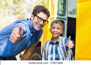 Portrait of smiling teacher and schoolboy showing thumbs up in front of school bus