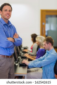 Portrait of a smiling teacher with young college students using computers in the computer room