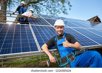 Portrait of smiling technician with electrical screwdriver showing thumb-up in front of unfinished high exterior solar panel photo voltaic system with team of workers on high platform.