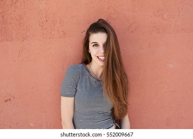 Portrait of smiling teen with long hair against of textured pink wall