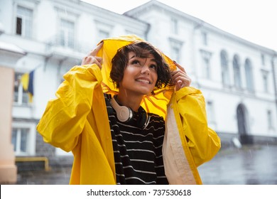 Portrait of a smiling teenage girl with headphones wearing raincoat outdoors