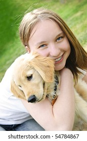 Portrait of smiling teenage girl holding golden retriever puppy