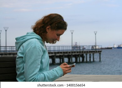 Portrait of a smiling teenage girl sitting on a bench in front of the Mediterranean sea in twilight and using a smarphone