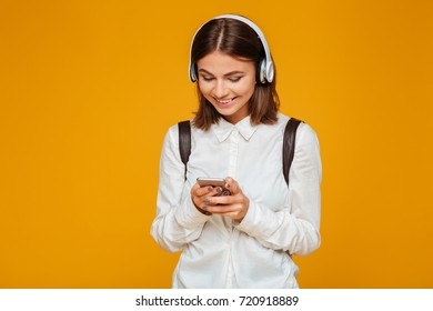 Portrait of a smiling teenage schoolgirl in uniform with headphones holding mobile phone isolated over orange background