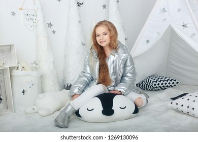 portrait of smiling teenager girl with long red hair in silver jacket in white christmas decorations