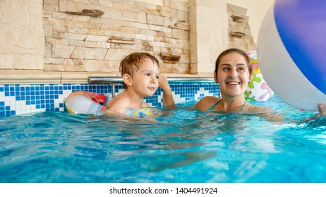 Portrait of smiling toddler boy playing with inflatable colorful beach ball with mother in indoors swimming pool