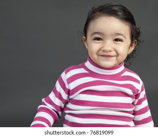 Portrait of a Smiling Toddler Girl on a Grey Background