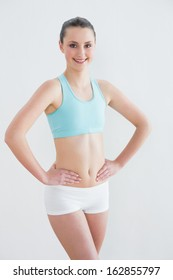 Portrait of a smiling toned young woman with hands on hips against wall in fitness studio