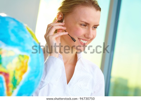 Portrait of smiling tour agent with headset consulting client online