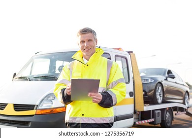 Portrait of smiling tow truck driver with clipboard against sky