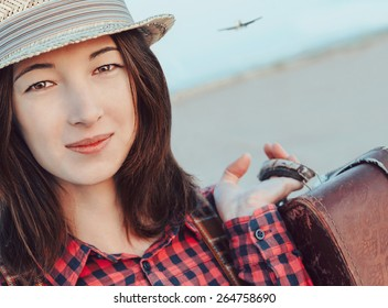 Portrait of smiling traveler young woman with suitcase. Airplane flying in the sky. Concept of travel