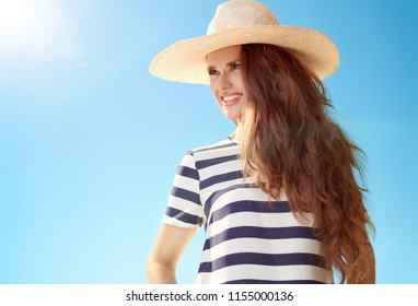 Portrait of smiling trendy woman in straw hat looking aside against blue sky