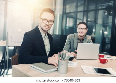 Portrait of smiling unshaven male working with serene affiliate while locating at table in office. Occupation and conversation concept