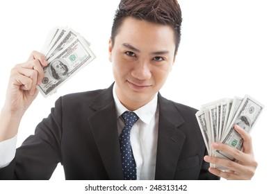 Portrait of smiling Vietnamese businessman with dollar bills in his hands