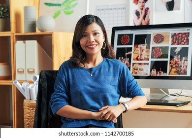 Portrait of smiling Vietnamese graphic designer at her table in office