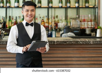 Portrait of smiling Vietnamese waiter with digital tablet standing at bar