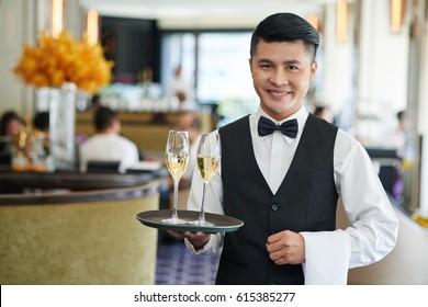 Portrait of smiling Vietnamese waiter serving drinks in restaurant