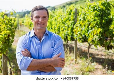 Portrait of smiling vintner standing with arms crossed in vineyard