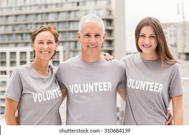 Portrait of smiling volunteers putting arms around each other on roof of building