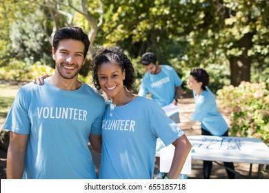 Portrait of smiling volunteers standing in the park