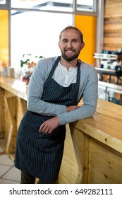 Portrait of smiling waiter leaning at counter in cafe