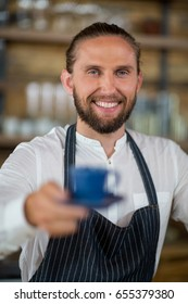 Portrait of smiling waiter offering cup of coffee in café