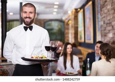 Retrato de un camarero sonriente que sirve la bandeja en el restaurante