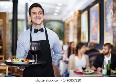 Portrait of smiling waiter with a serving tray in the restaurant
