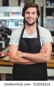 Portrait of smiling waiter standing with arm crossed in cafe