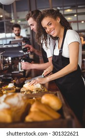 Portrait of smiling waitress cutting bread in front of colleague at coffee shop