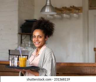 Portrait of a smiling waitress holding tray of drinks in restaurant