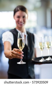 Portrait of smiling waitress offering a glass of champagne in restaurant