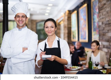 Portrait of smiling waitress with professional chef at restaurant. Focus on woman