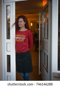 Portrait of smiling waitress standing at entrance of cafe