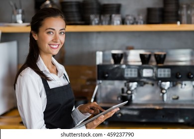Portrait of smiling waitress using digital tablet in cafe